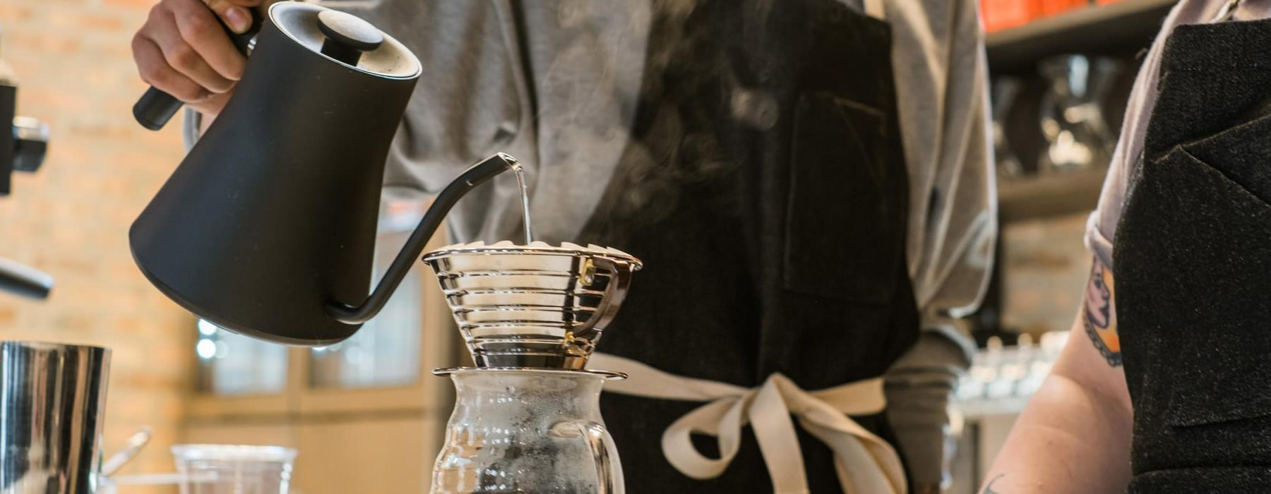 barista making pour over coffee in coffee shop
